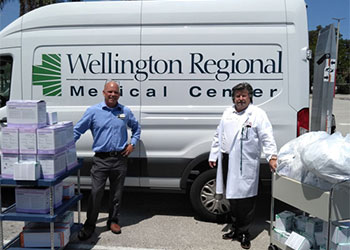 James Watson, supply chain director at Wellington Regional Medical Center, picks up medical supplies from Ed Willey, dean of Health Sciences at PBSC.